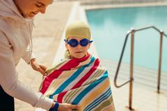 Boy after swimming lessons. Woman wrapping towel on boy after swimming in the pool. Boy wrapped in towel with coach after swimming class royalty free stock photos