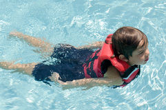 Boy swimming in life vest Stock Photography