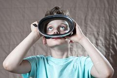 Boy in a swimming mask looking up. From the water stock photos