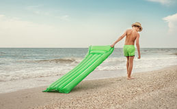 Boy with swimming mattress walks on sand sea beach Stock Photos