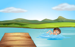 A boy swimming near the diving board Stock Images