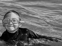 Boy Swimming in the Ocean. A young boy grins as he swims in the ocean with his goggles and wetsuit Royalty Free Stock Photography