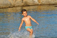 Boy in swimming pants running through the water Royalty Free Stock Images