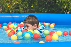 Boy swimming on a plastic pool. With multicolored plastic balls Royalty Free Stock Photography