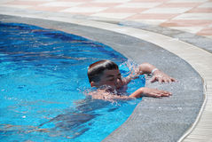 Boy in swimming in the pool Stock Images