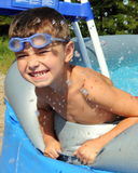 Boy in the swimming pool. Happy little boy wearing blue goggles splashing the water in the swimming pool stock image