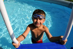 Boy in the swimming pool. Little boy wearing blue goggles getting out of the swimming pool Royalty Free Stock Photography