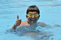 Boy in swimming in the pool. Happy boy in swimming in the outdoor pool. ok sign hand Royalty Free Stock Image