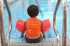 Boy at swimming pool. Back view of boy with swimsuit sitting at the swimming pool Stock Image