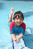 Boy at swimming pool. Boy wearing blue & red swim suit at the pool Royalty Free Stock Image