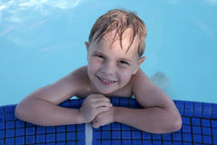 Boy in swimming pool. A 5-year-old cute blonde boy shows his big smile at the edge of a beautiful blue swimming pool Stock Photography