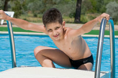 Boy at the swimming pool. A boy is enjoying a sea resort at a swimming pool Stock Image