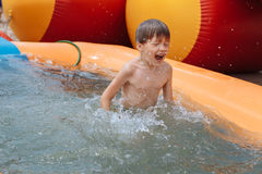 The boy is swimming in the pool. A boy bathes in the pool, rejoices, plays stock photo