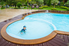 Boy in swimming pool. And double swing in background Stock Images