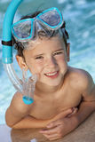 Boy In A Swimming Pool with Goggles and Snorkel. A happy young boy child relaxing on the side of a swimming pool wearing blue goggles and snorkel Stock Photo