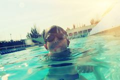 Boy in swimming pool half in water instagram style image Stock Images