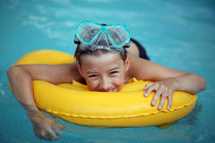 Boy in swimming pool and lifebuoy Stock Photos