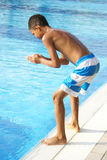 Boy at swimming pool. Boy preparing to jump into swimming pool Royalty Free Stock Images