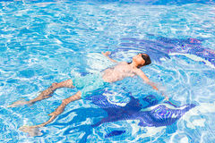Boy swimming in pool. Boy relaxing in cool water of pool Stock Image