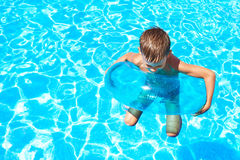 Boy swimming into pool Stock Photos