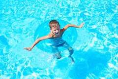 Boy swimming into pool Stock Image