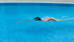 A boy is swimming in a pool. Side view. Boy is swimming the breaststroke in an outdoor pool. Side view Royalty Free Stock Photo