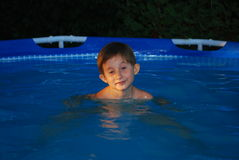 Boy in swimming pool smiles. A boy in a swimming pool at sunset smiles at the camera Royalty Free Stock Image