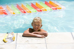 Boy (7-9) in swimming pool, smiling, portrait Royalty Free Stock Image
