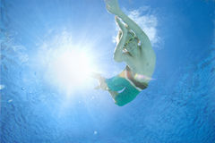 Boy (10-12) in swimming pool, smiling, portrait, underwater view (lens flare) Royalty Free Stock Photos