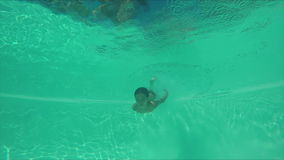 Boy swimming in the pool under water stock footage