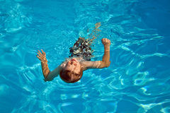 Boy swimming in the pool during vacation Stock Photos