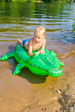 Boy swimming in the river with inflatable crocodile Stock Images