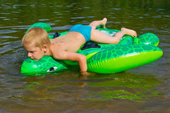 Boy swimming in the river with inflatable tur Royalty Free Stock Photos