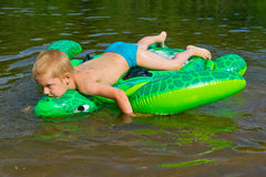 Boy swimming in the river with inflatable tur Stock Photo