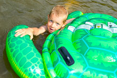 Boy swimming in the river with inflatable tur Stock Photos