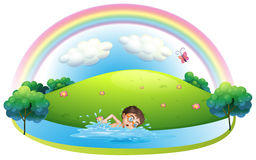 A boy swimming in the river near the hill Stock Images