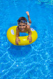Boy swimming on rubber ring in pool Stock Photo