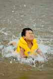 Boy swimming in sea. Picture of a little chinese boy swimming in sea with water splashing Stock Photography
