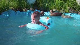 The boy is swimming in a small pond. The child enjoys cool water on a hot summer day. Happy childhood. Flowers and grass. The boy is swimming in a small pond stock footage