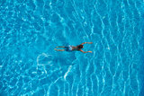 Boy is swimming in a swimming pool. Top view. Royalty Free Stock Images