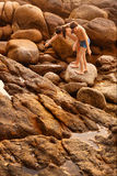 Boy in swimming trunks climbing rocks Royalty Free Stock Photo