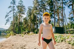 A boy in swimming trunks stands on the sandy shore. A boy of five years in swimming trunks stands on the sandy shore of the lake in the summer stock images