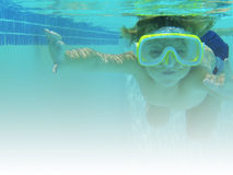 Boy swimming underwater. Young boy swimming in a pool, underwater with a scuba mask on Royalty Free Stock Images