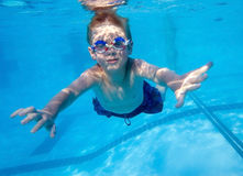 Boy swimming underwater. In swimming pool Royalty Free Stock Photography