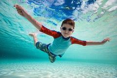 Boy swimming underwater. Cute little boy swimming underwater in tropical sea Stock Photo