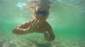 Boy swimming underwater stock video footage