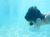 Boy swimming underwater in ocean Stock Photos