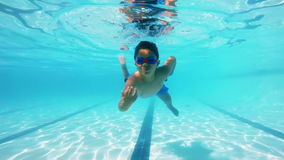 Boy swimming underwater in pool. Determined boy swimming underwater in pool stock video
