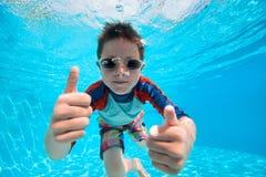 Boy swimming underwater. Portrait of a cute little boy swimming underwater Royalty Free Stock Photos