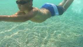 Boy swimming underwater. In pure blue sea water stock footage